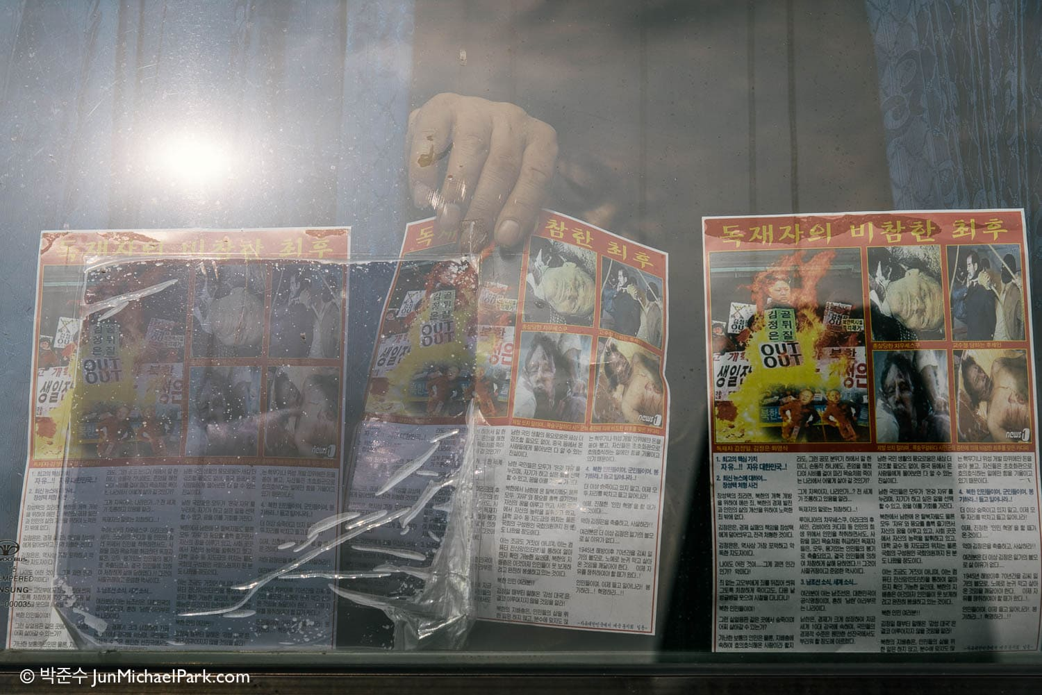 "An activist shows off the much controversial Anti-North Korea propaganda leaflets through the bus window. The title reads: ""The Miserable End of a Dictator."" Imjingak Peace Park, Paju, South Korea, Oct 25, 2014."