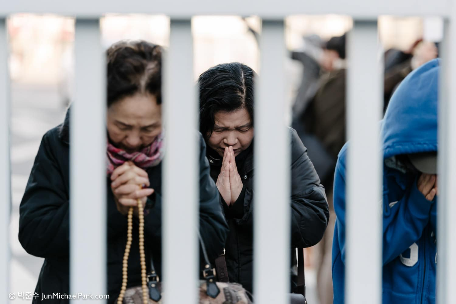 Mothers and grandmothers of examinees pray outside the school gate while their children take the Korea College Entrance Exam. Seoul, 2014.