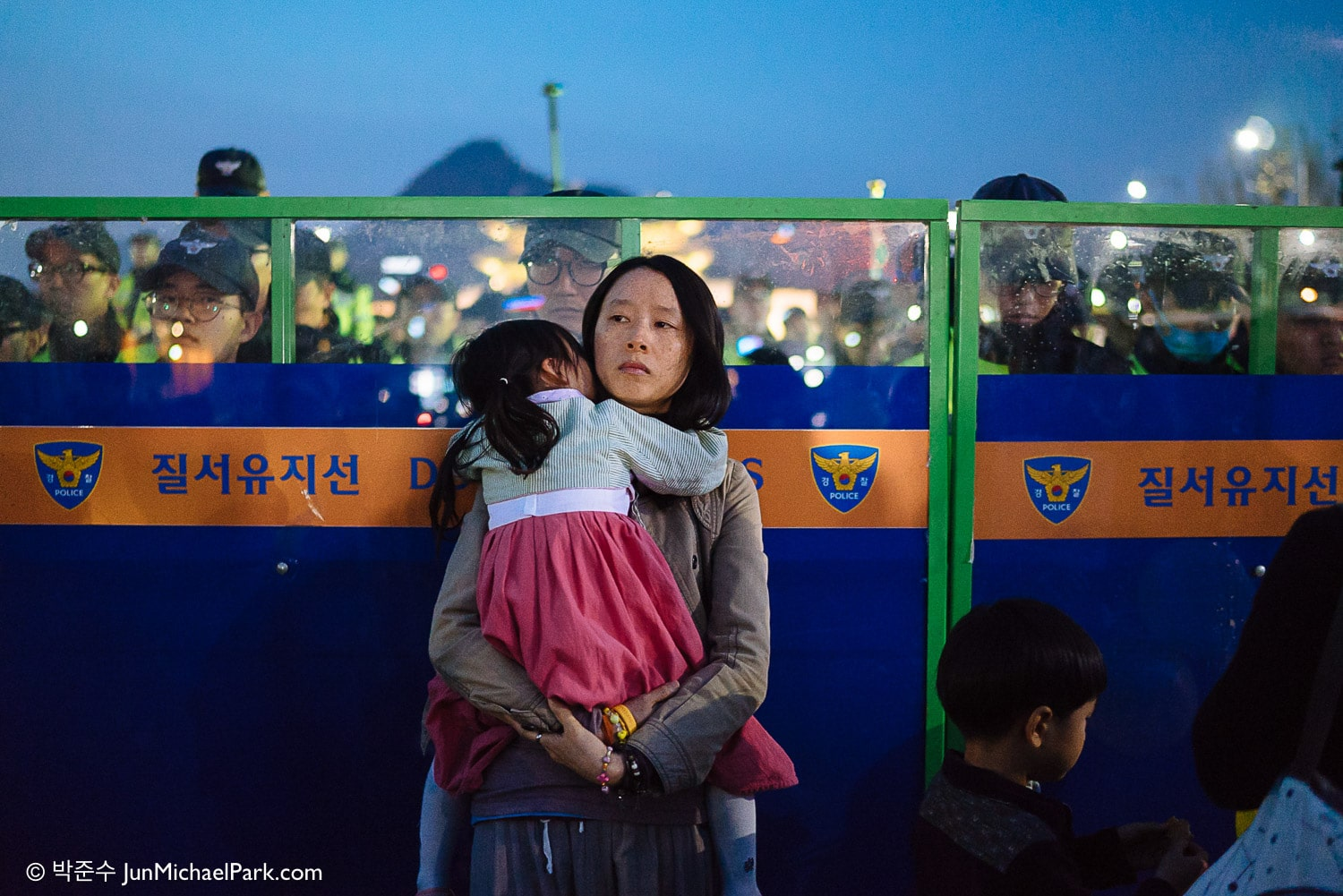 A mother stands in front of the police line in solidarity with Sewol families during a protest around the one year anniversary.