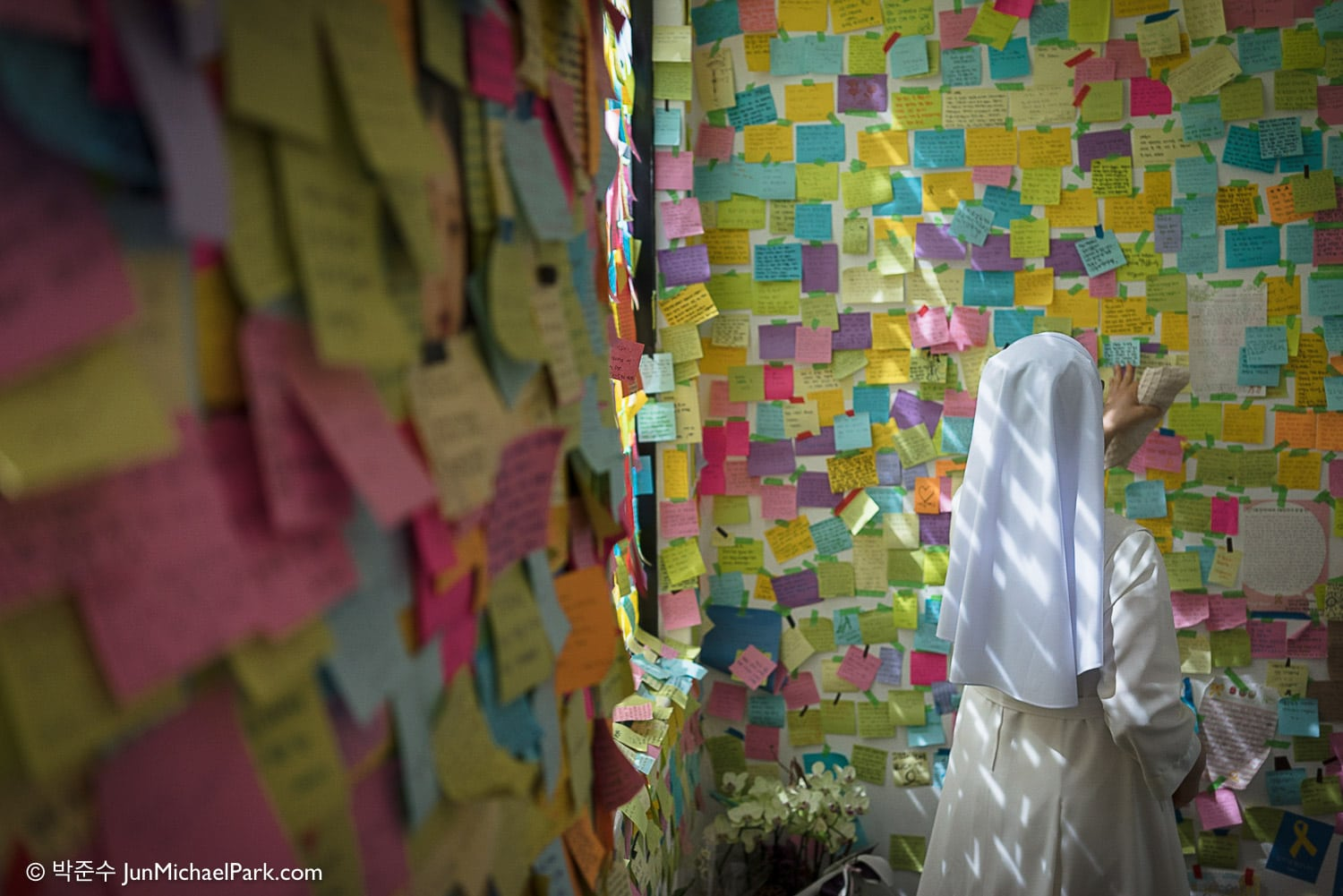 At a Sewol student victim's posthumous art exhibition, a catholic nun carefully tends tribute notes left by visitors.