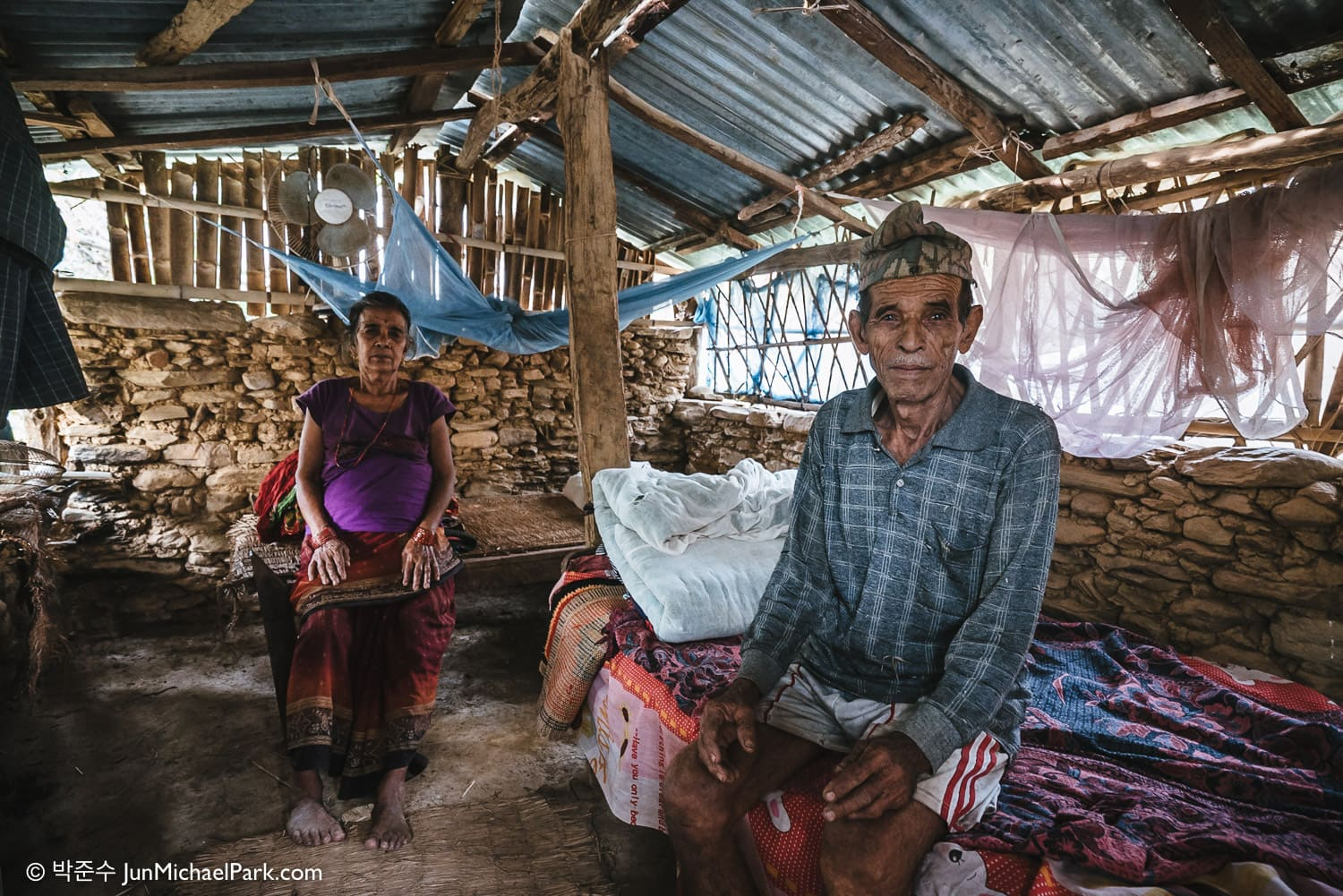 Rub Bahadur Thapa, 78(right), and Echha Kumari Thapa, 70, live in a remote village in Bhanu, Tanahun District, Nepal. Traumatized by the earthquake and aftershocks, they are too afraid to sleep in their house. Instead they sleep in a small barn with a makeshift tinplate roof. 28.10.15