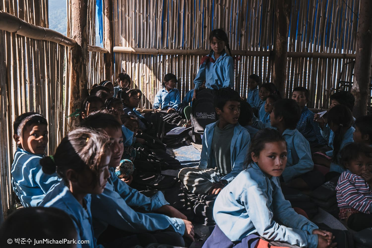 Students wait for visitors in a classroom made of bamboo tree and tarpaulin  canopy during a recess at Mangal Bhairav Primary School on a mountain top, Katarche, Syaule, Sindhupalchok District, Nepal. 04.11.15